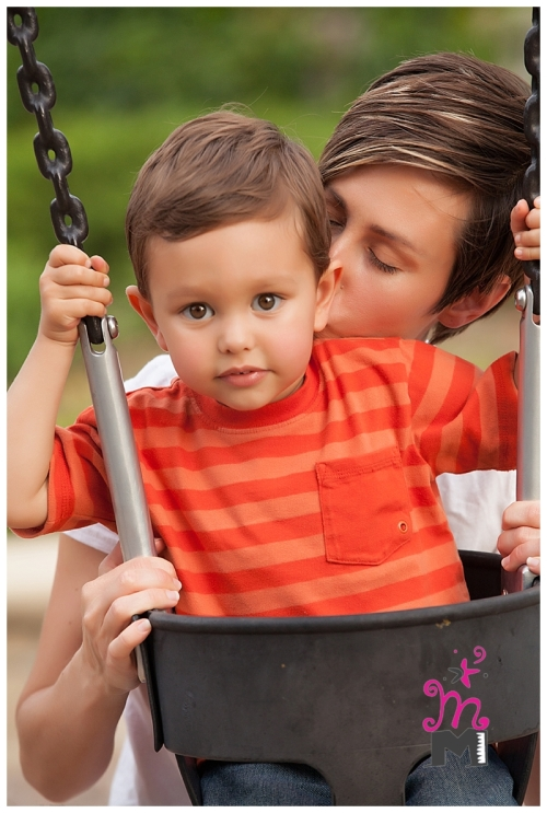Young mom kissing child in swing as he looks at camera