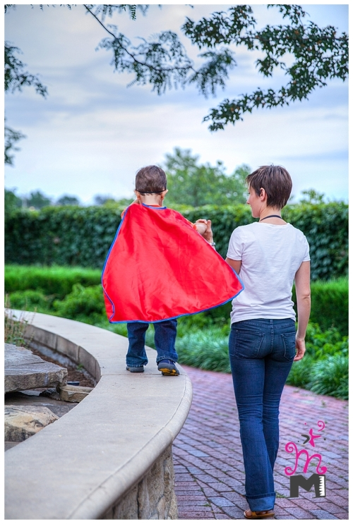 Young mom holds son's hand as he walks on wall beside her in cape