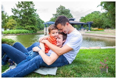 Family hug with young parents and young son on green grass with lake in background