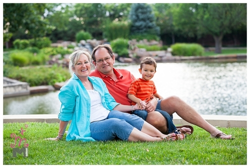 Grandparents with grandson sitting on grass with lake in background